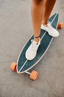 Mujer en zapatillas montando patineta al aire libre en la superficie de asfalto.