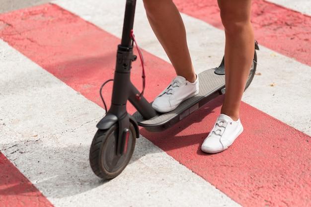 Mujer con zapatillas de tenis montando scooter
