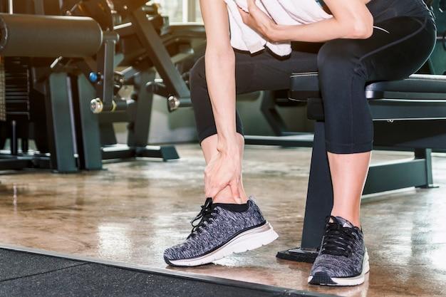 Mujer en zapatillas tocando su pierna y tobillo con dolor