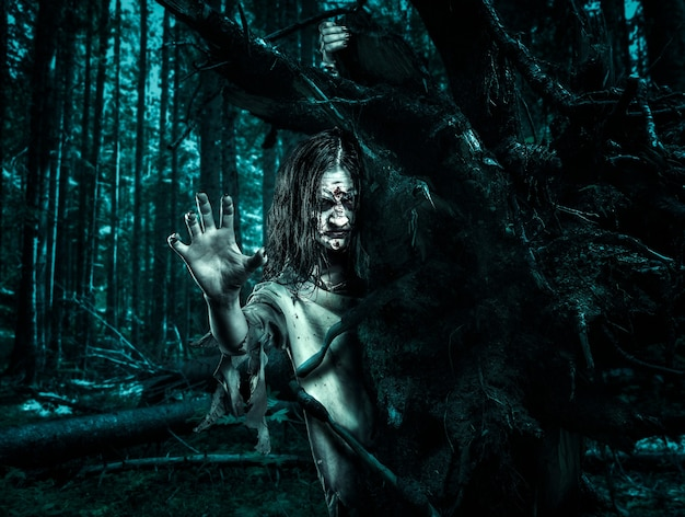 Mujer zombie en una bata sucia mira desde detrás de un árbol. víspera de todos los santos.