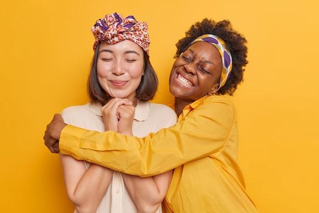 Las mujeres se abrazan tienen una relación amistosa, felices de pasar el tiempo libre juntas, usan ropa elegante, posan en amarillo vivo