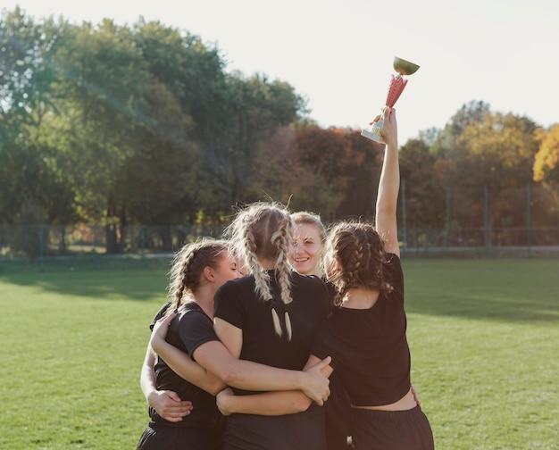 Mujeres abrazando y sosteniendo un trofeo deportivo