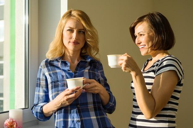 Las mujeres adultas beben café hablar risa