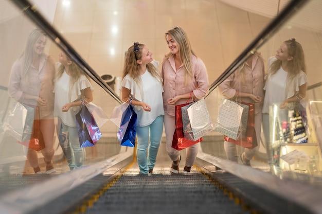 Mujeres adultas elegantes felices de comprar juntas