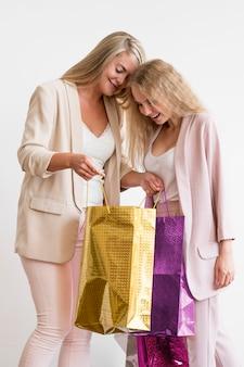 Mujeres adultas hermosas que comprueban compras