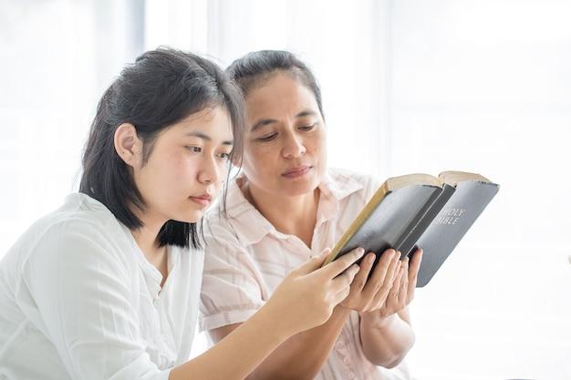 Las mujeres adultas leen la santa biblia y comparten el evangelio con los jóvenes. los libros de la biblia, conceptos del cristianismo.