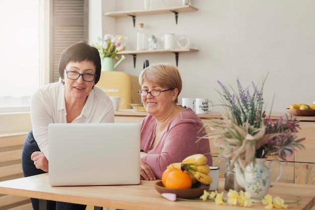 Mujeres adultas mirando una computadora portátil