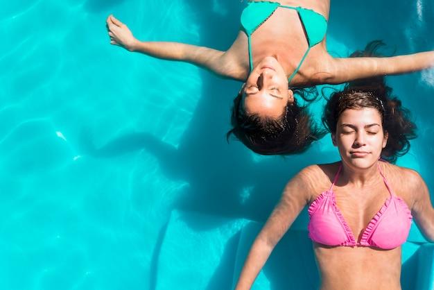 Mujeres adultas con los ojos cerrados enfriándose en la piscina.