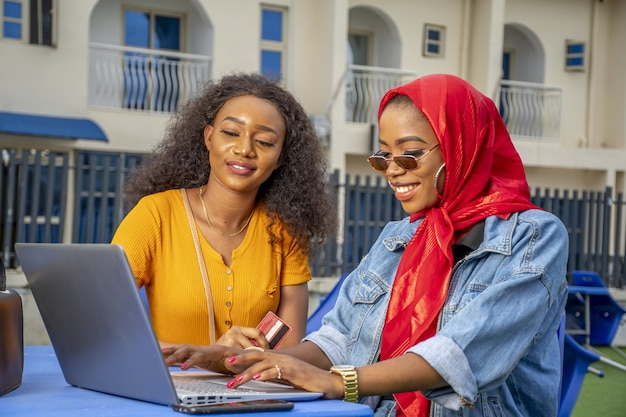 Mujeres africanas de compras en línea mientras está sentado en un café