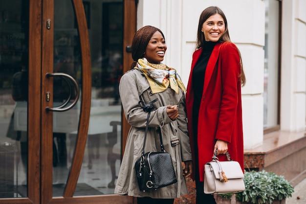 Mujeres afroamericanas y caucásicas en la calle.