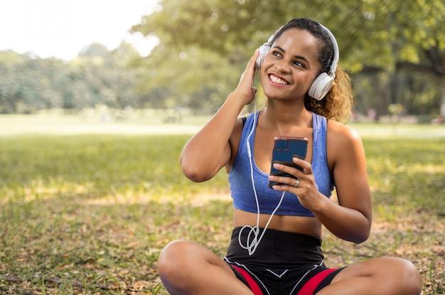 Mujeres afroamericanas sentadas con felices sonrientes y escuchando la música en el parque para un estilo de vida relajado