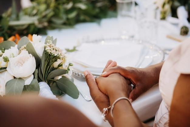 Las mujeres afroamericanas sostienen sus manos juntas sentadas en la mesa de la cena