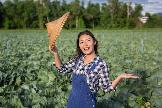Mujeres agricultoras que están contentas con los cultivos en sus jardines.