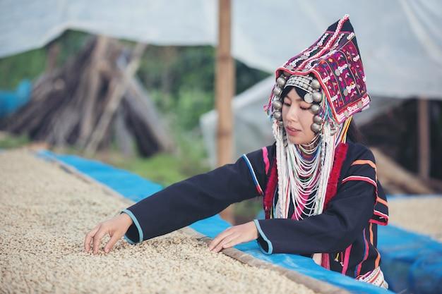 Las mujeres akha sonrieron y admiraron el café.