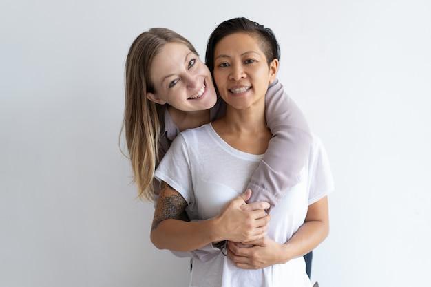Mujeres alegres abrazando y mirando a cámara