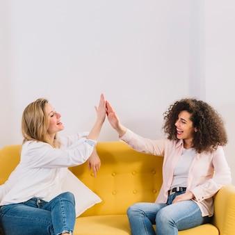 Mujeres alegres alto-fiving en el sofá amarillo