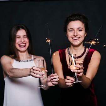 Mujeres alegres con copas de champán y bengalas.
