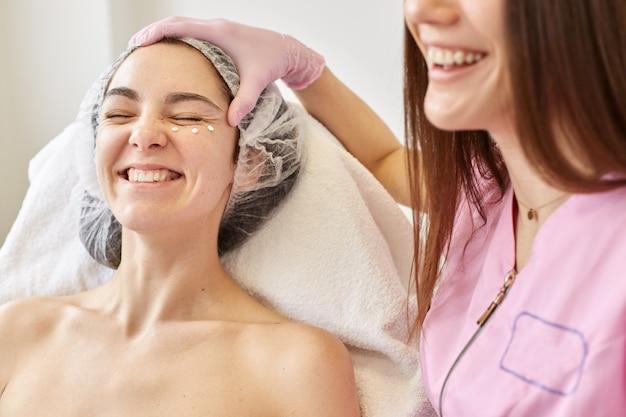 Las mujeres alegres y felices tienen buen humor, se ríen sinceramente. esteticista sonriente y experimentado hace que su cliente sea más bella