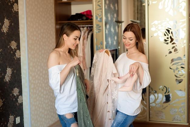 Mujeres alegres jovenes que sostienen dos vestidos brillantes coloridos y que eligen qué ponerse.