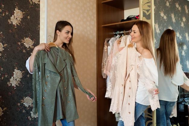 Mujeres alegres jóvenes sosteniendo dos coloridos vestidos brillantes y eligiendo qué ponerse