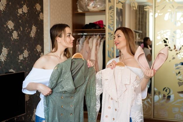 Mujeres alegres jóvenes sosteniendo dos vestidos de colores brillantes y eligiendo qué ponerse.
