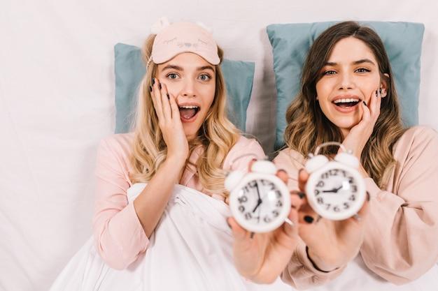 Mujeres alegres en pijama posando con relojes