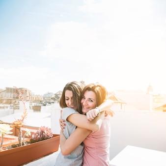 Mujeres alegres que abrazan en la calle