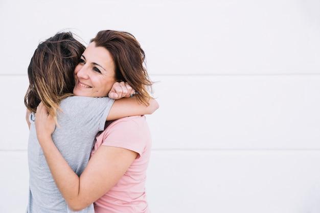 Mujeres alegres que abrazan cerca de la pared blanca