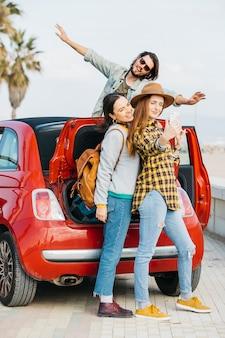 Mujeres alegres que toman autofotos en un teléfono inteligente cerca del maletero del coche y el hombre que se inclina hacia fuera desde el auto