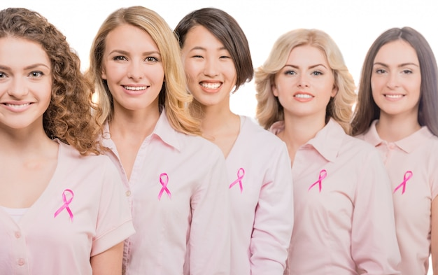 Mujeres alegres que usan cintas de color rosa para apoyar el pecho.