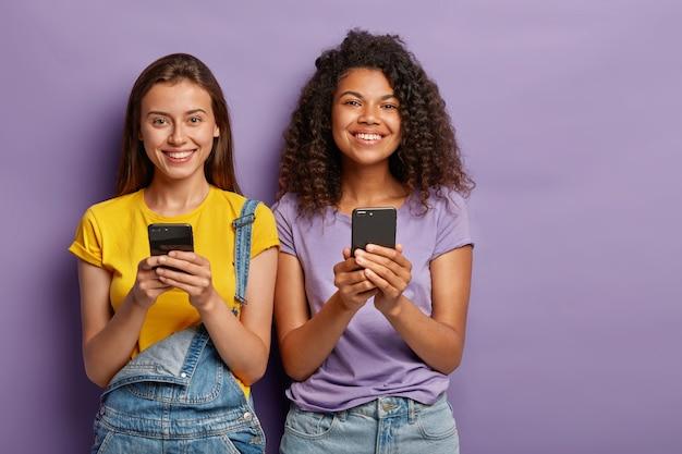 Mujeres alegres de raza mixta que siempre están en línea, usan teléfonos móviles para entretenerse y charlar en las redes sociales