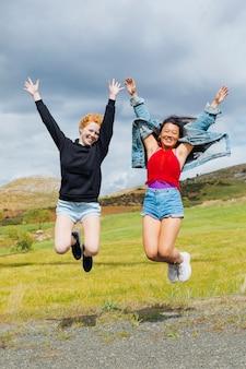 Mujeres alegres saltando en la carretera
