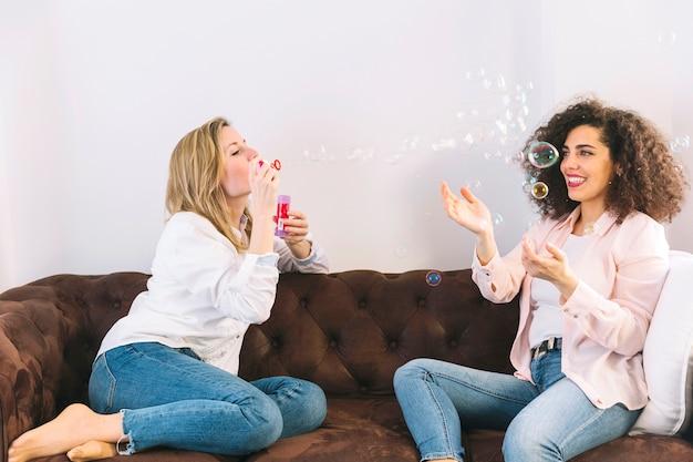 Mujeres alegres soplando y atrapando burbujas