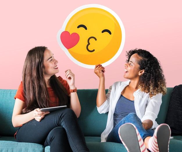 Mujeres alegres sosteniendo un icono de emoticon besándose