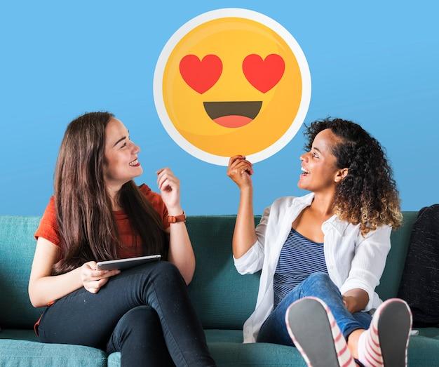 Mujeres alegres sosteniendo un icono de emoticon de ojos de corazón