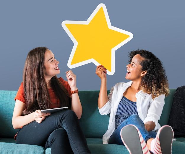 Mujeres alegres sosteniendo un icono de estrella dorada
