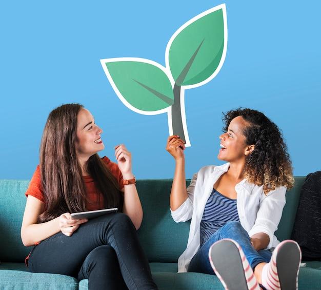 Mujeres alegres sosteniendo un icono de planta