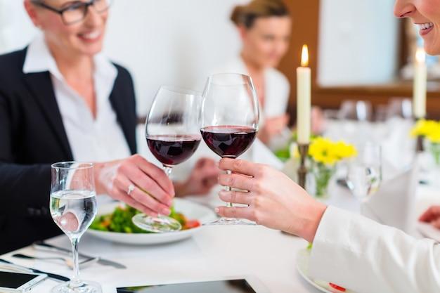 Mujeres en almuerzo de negocios brindando con vino.