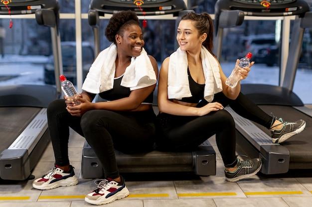 Mujeres de alto ángulo en el gimnasio en el descanso