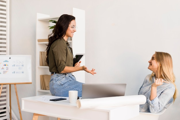 Mujeres de alto ángulo en la oficina hablando