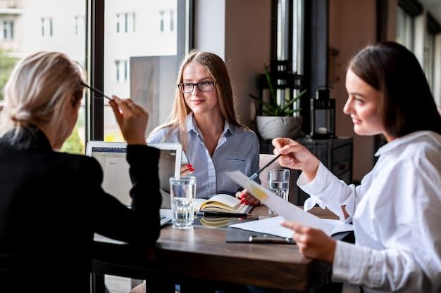 Mujeres de alto ángulo en la oficina planeando juntas