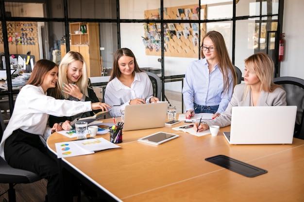 Mujeres de alto ángulo reunidas en el trabajo