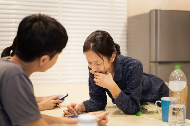 Mujeres con amigos compartiendo redes sociales en teléfonos inteligentes en casa