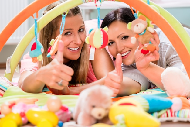 Mujeres amueblando la habitación del bebé preparando bar de juegos para los sucklings.