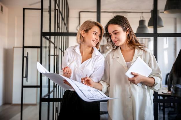 Mujeres de ángulo bajo que verifican resultados de negocios
