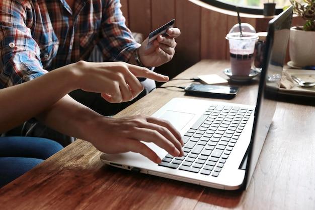 Las mujeres apuntan a ordenar al hombre que compre en línea con tarjeta de crédito y computadora portátil