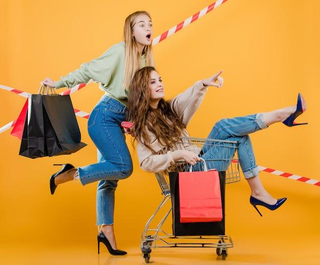 Mujeres apuntando a copyspace con carrito lleno de bolsas de compras y cinta de señal aislada sobre amarillo