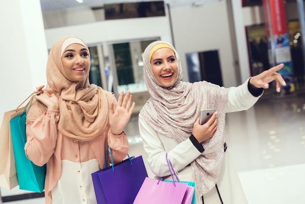Mujeres árabes con paquetes de pie en el centro comercial.