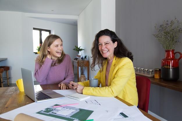 Mujeres arquitectas trabajando con dibujos y riendo.