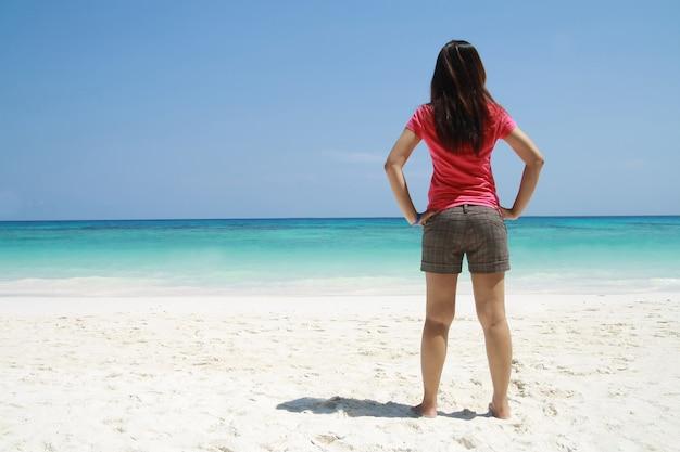 Las mujeres de asia se paran en la playa